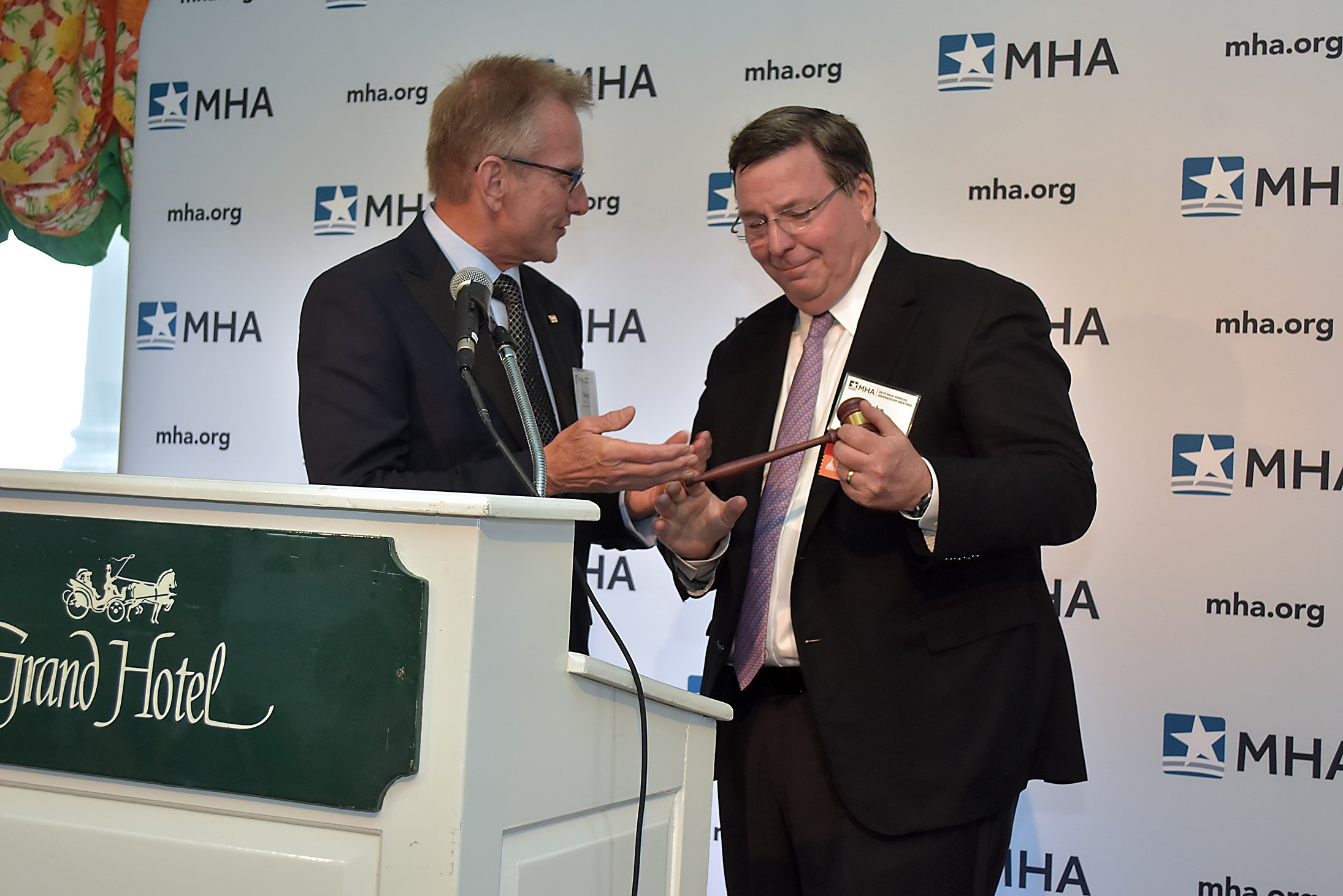 Gregory R. Lane, past chair, presents the gavel to new MHA Board of Trustees chair, John Fox.